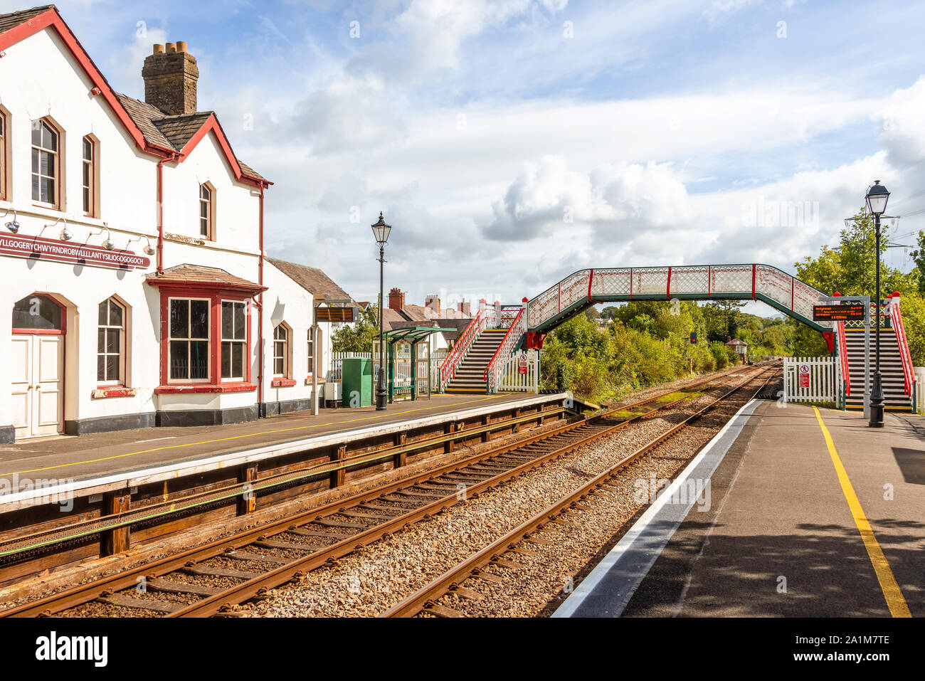 Station building and footbridge at  Llanfairpwllgwyngyll, in Wales known to have the longest place name in the UK. A blue sky is overhead. Stock Photo