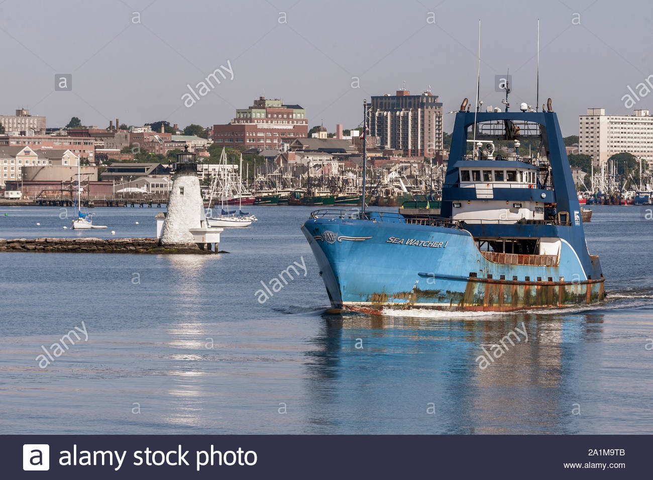 New Bedford, Massachusetts, USA – July 26, 2019: Clammer Sea Watcher I, hailing port Atlantic City, New Jersey, passing lighthouse on her way out of N Stock Photo
