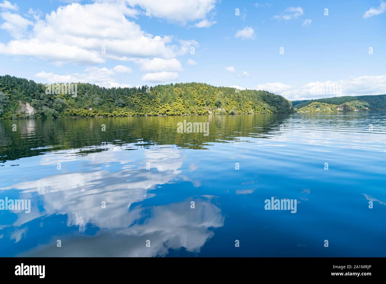 Reflected lake edge and white clouds on idyllic Lake Rotoiti near Rotorua New Zealand. Stock Photo