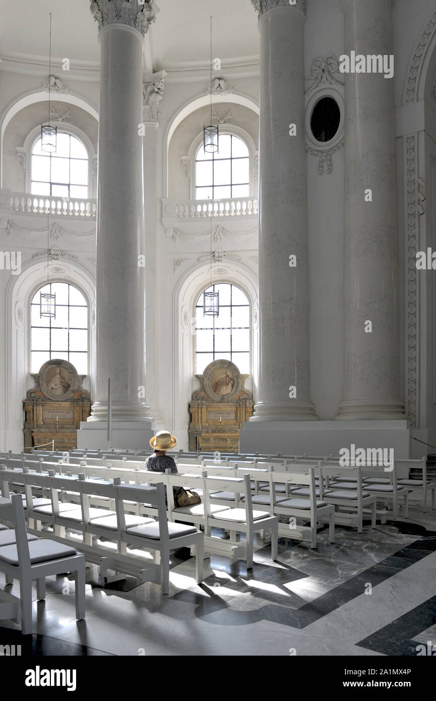 A women is sitting on a bank in the cathedral of St. Blasien (Black Forest, Germany). Stock Photo