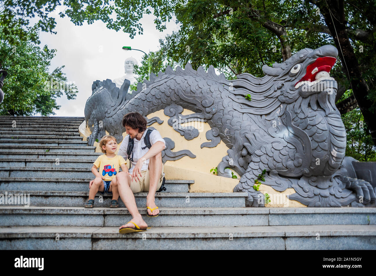 Happy tourists dad and son in Long Son Pagoda. Travel to Asia concept. Traveling with a baby concept. Stock Photo