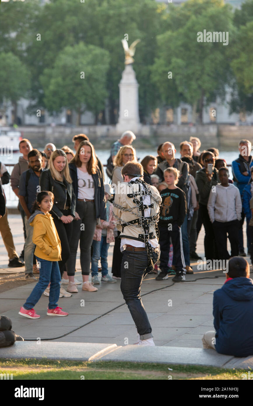 Straightjacked street performer and busker performing on South Bank London. Buskers supported by the Mayor of London. Audience engaged. Foot elevated. Stock Photo