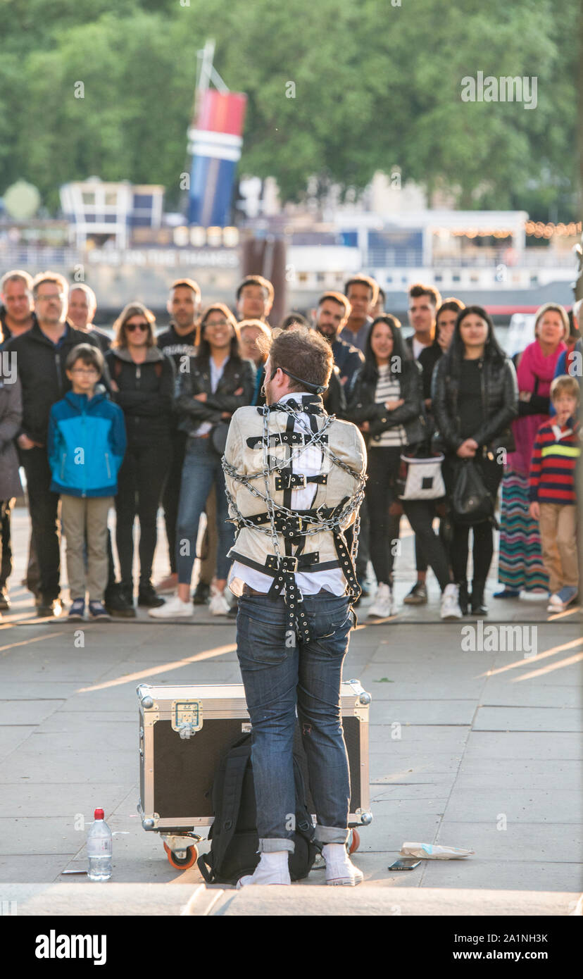Straightjacked street performer and busker performing on South Bank London. Buskers supported by the Mayor of London. Audience engaged. Feet on ground Stock Photo