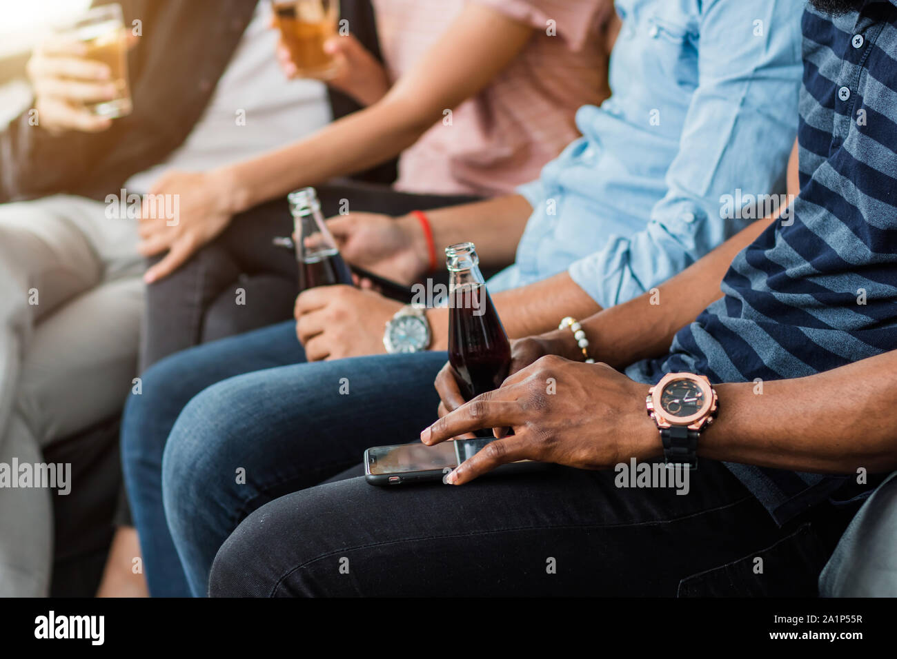 Cropped shot of young african man wearing stylish wrist watch, holding in hand bottle with soft drink and using mobile phone, sitting on sofa with fri Stock Photo