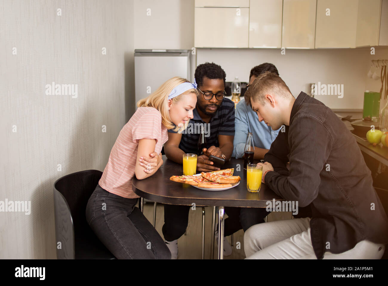 Shot of students sitting at table in hostel kitchen and looking at screen of mobile phone together. Friends watching something on smartphone while hav Stock Photo