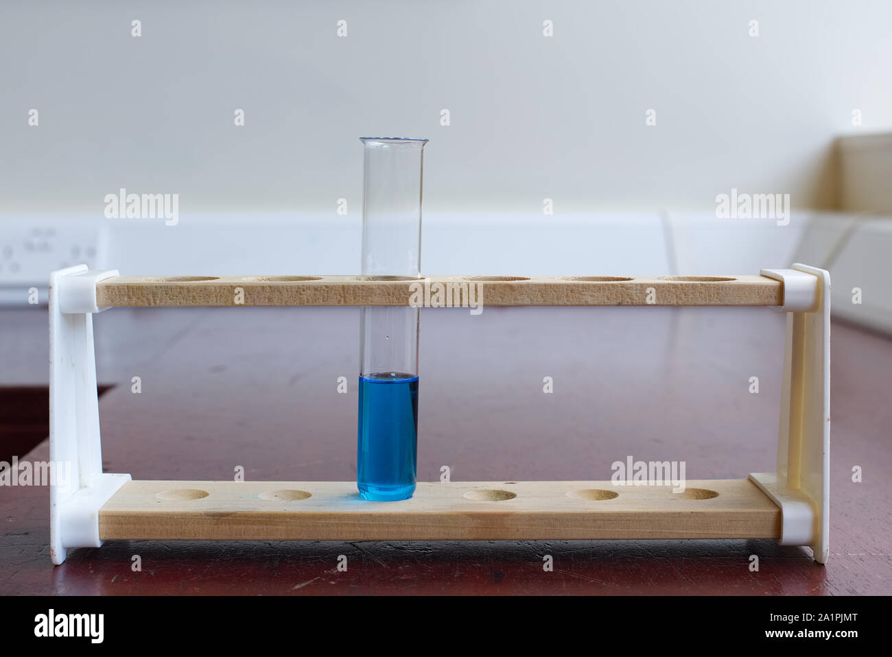 Wooden test tube rack with boiling tube of copper sulfate solution in an old school science laboratory. Science education lab concept Stock Photo