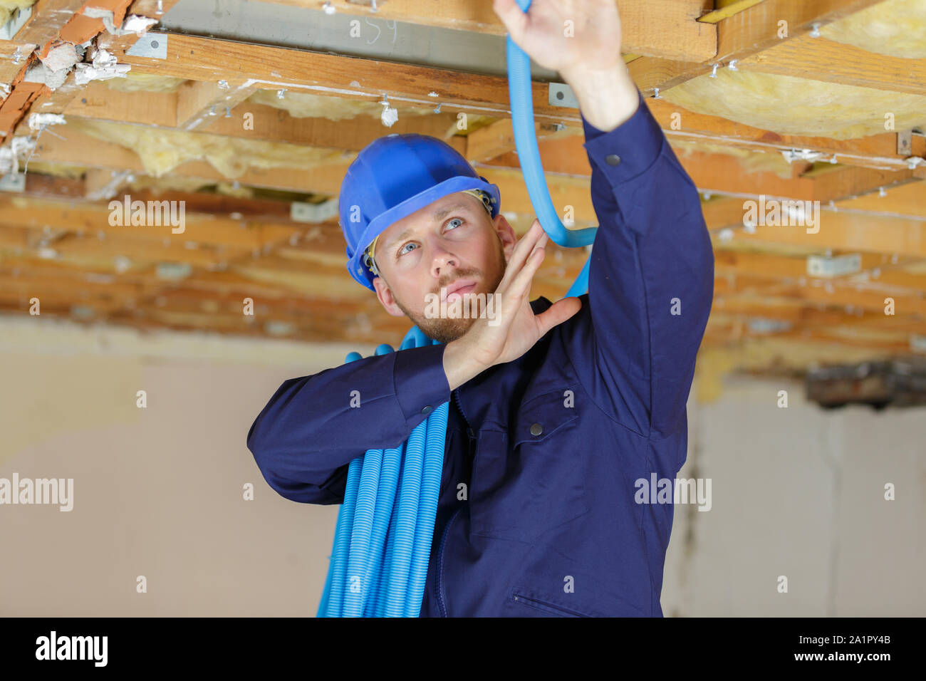 builder installing cables into roofspace Stock Photo