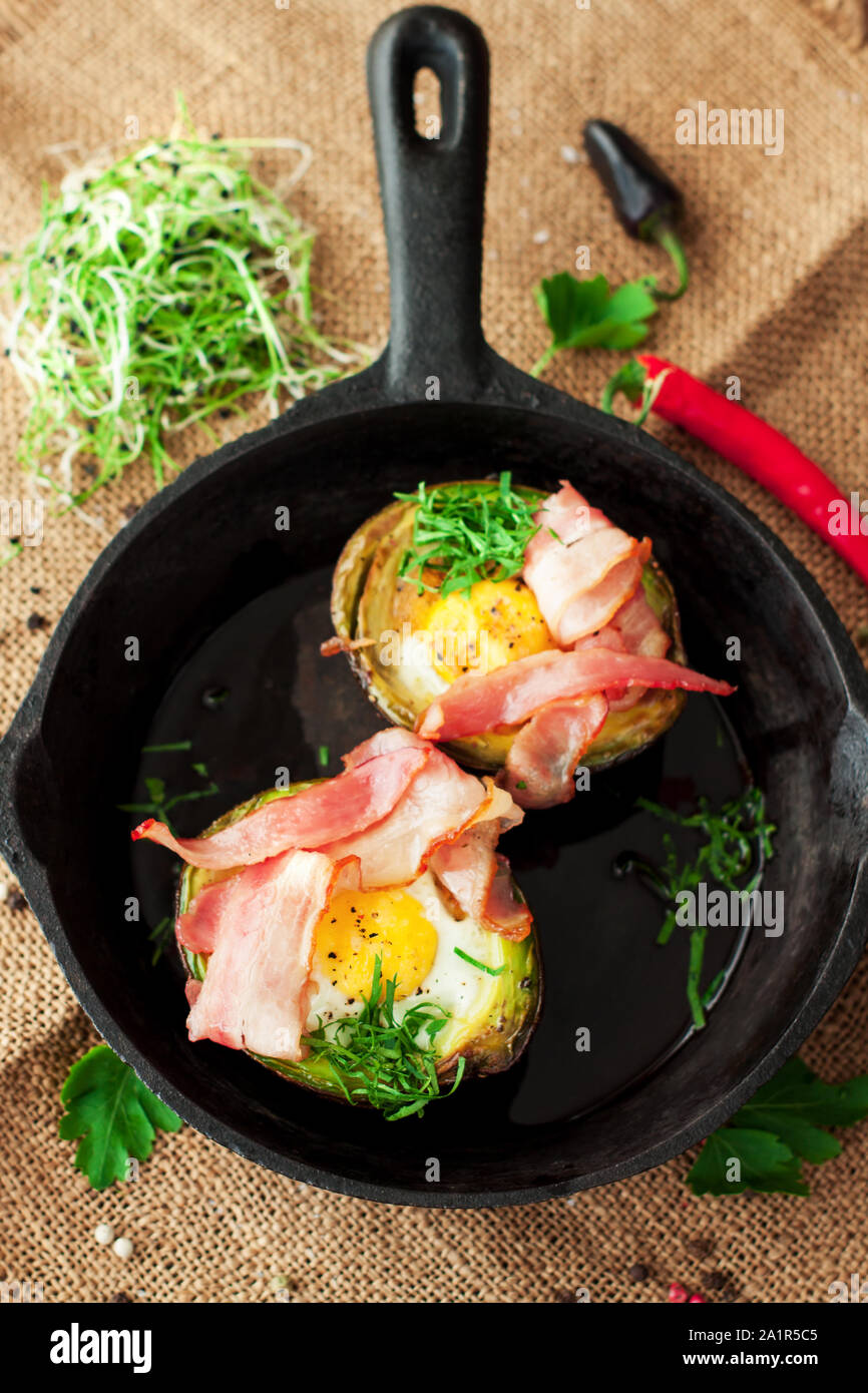 Two baked eggs in avocado with bacon in iron pan garnished with parsley Stock Photo