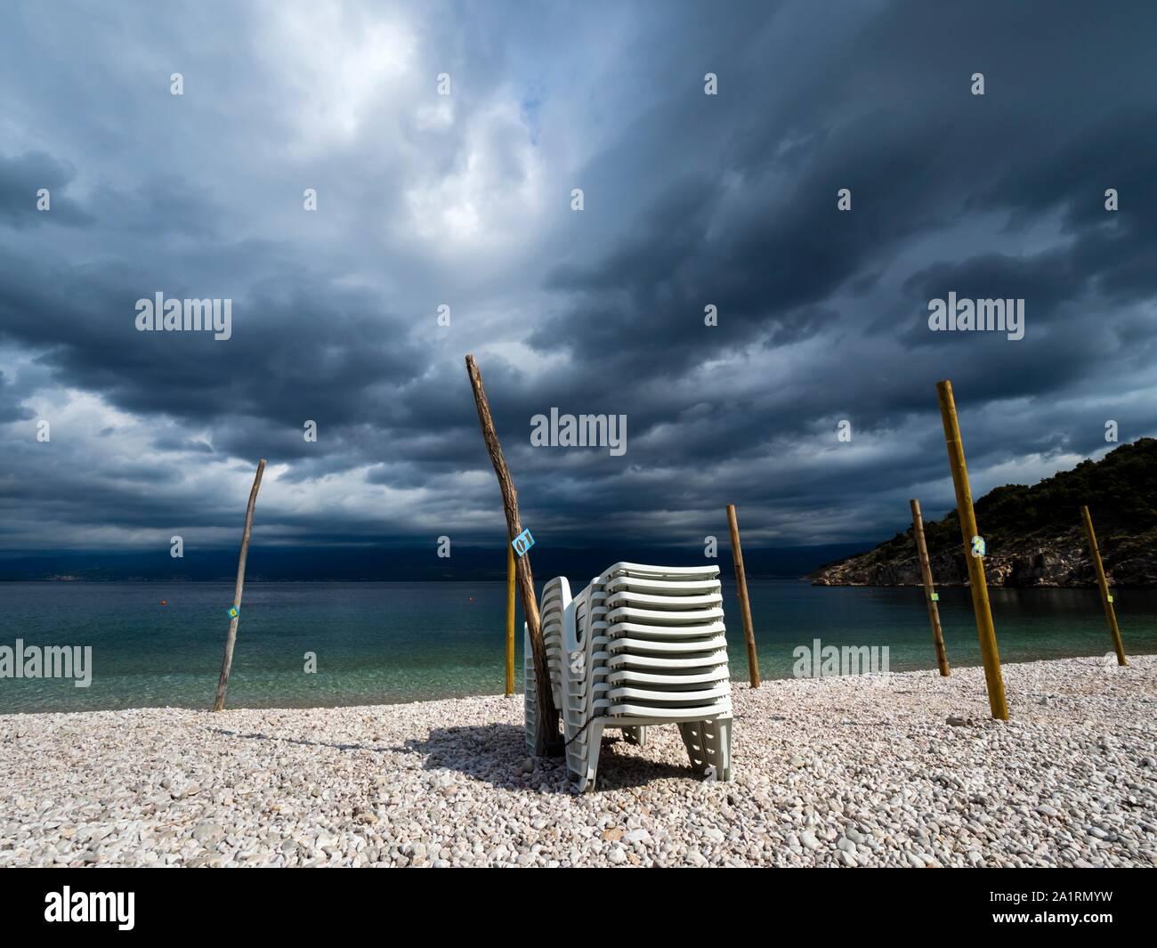 Summer end on beach piled deckchairs stormy dark sky in background empty Stock Photo