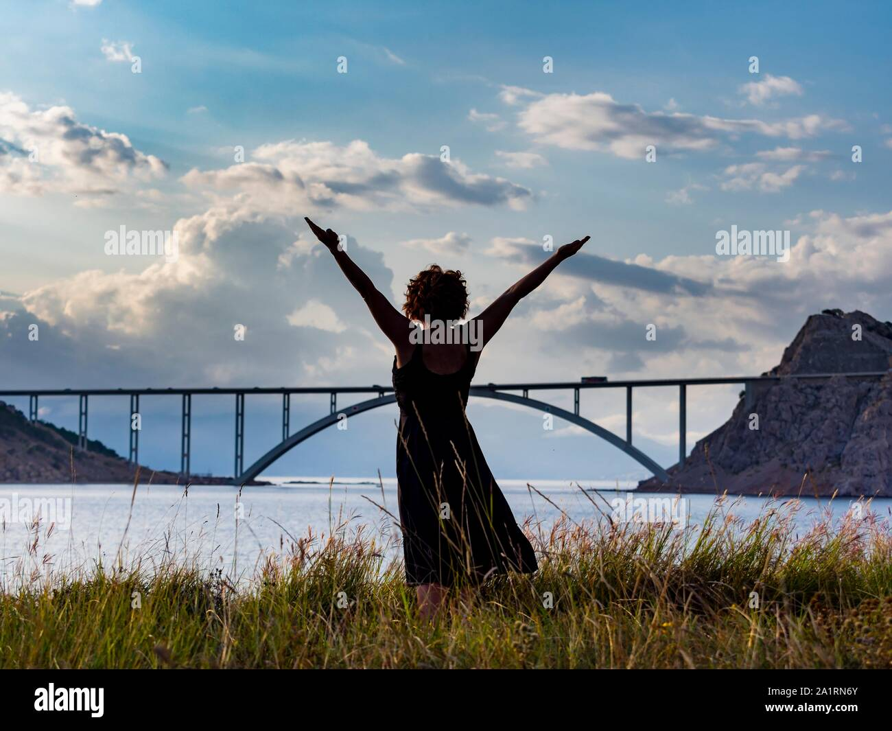 Hand spread spreading away and up upwards in late afternoon before distant bridge and numerous White clouds silhouette nobody Stock Photo