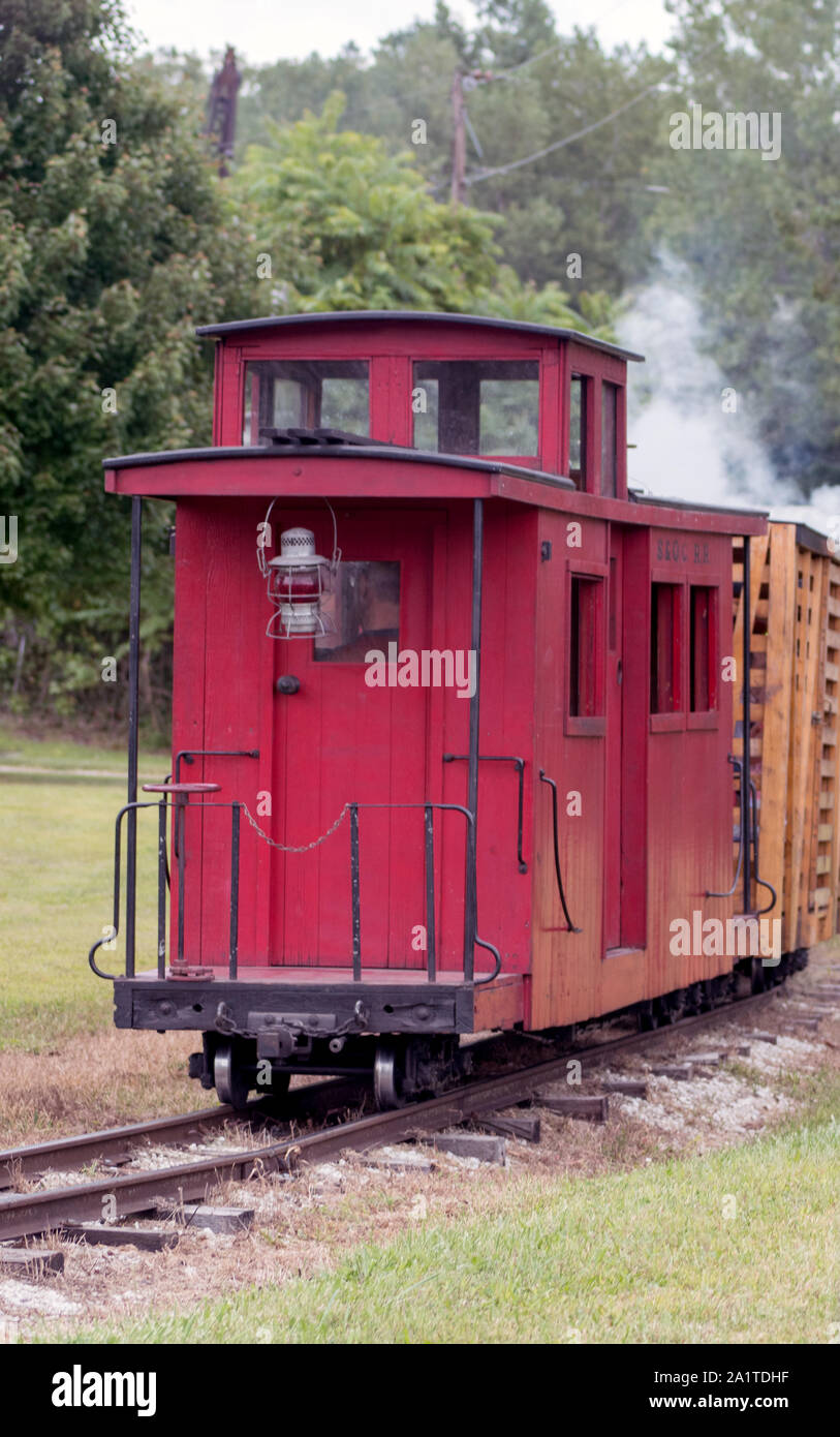 A little red caboose car is the last car on this miniature steam train ride Stock Photo