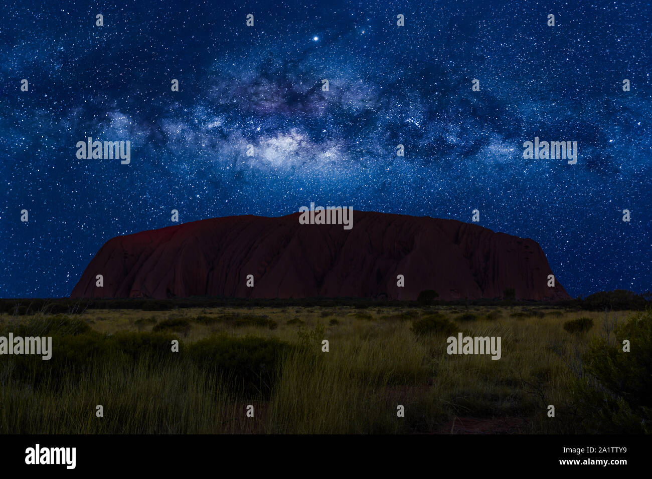 Spectacular Uluru by night with milky way, stars field and galaxies. Uluru-Kata Tjuta National Park in Northern Territory, Central Australia. Stock Photo