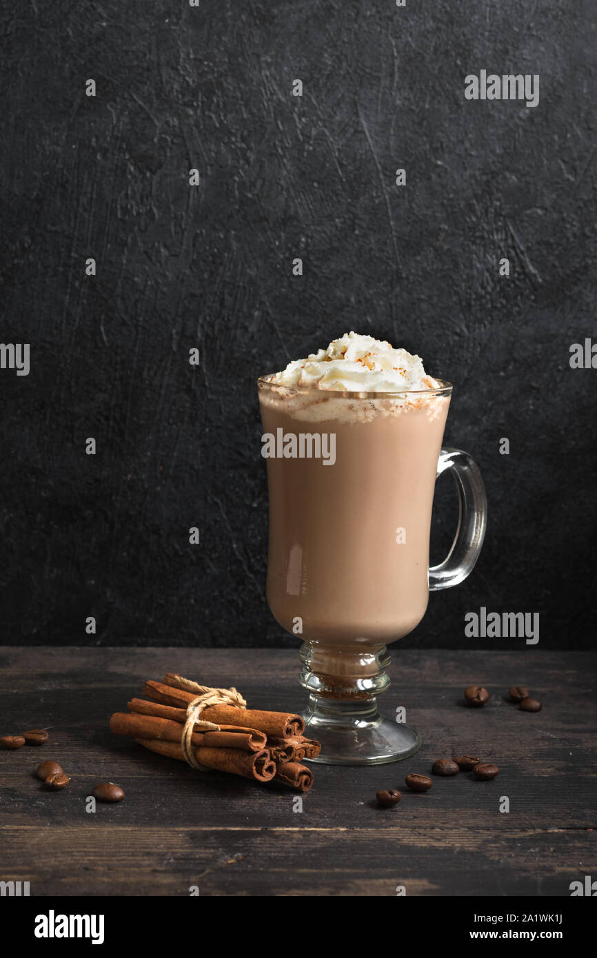 Irish Coffee with whipped cream on black wooden background, copy space. Stock Photo