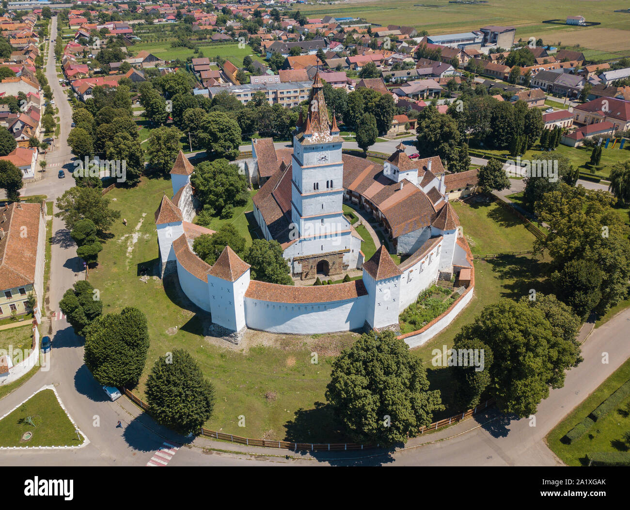 Aerial view of fortified church surrounded powerful thick walls in Transylvania overlooking the village in a beautiful summer day. Romania Stock Photo