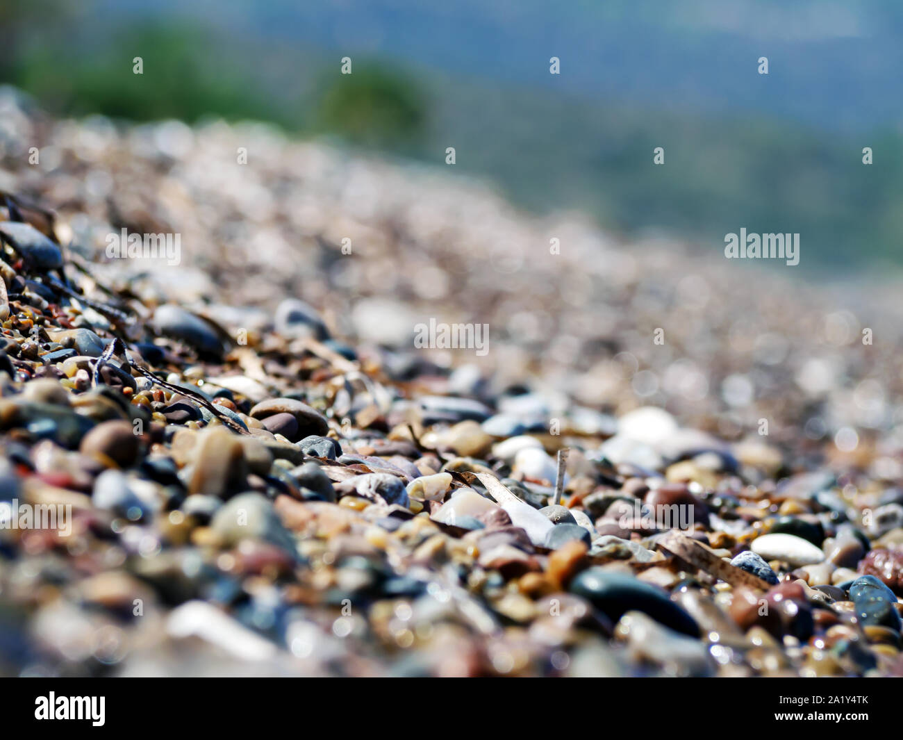 Pattern with turquoise sea stones beach on for design. Beautiful gravel background. Stone texture. Horizon sea water landscape. Image For desktop, wallpapers, banner. Copy space, selective focus Stock Photo