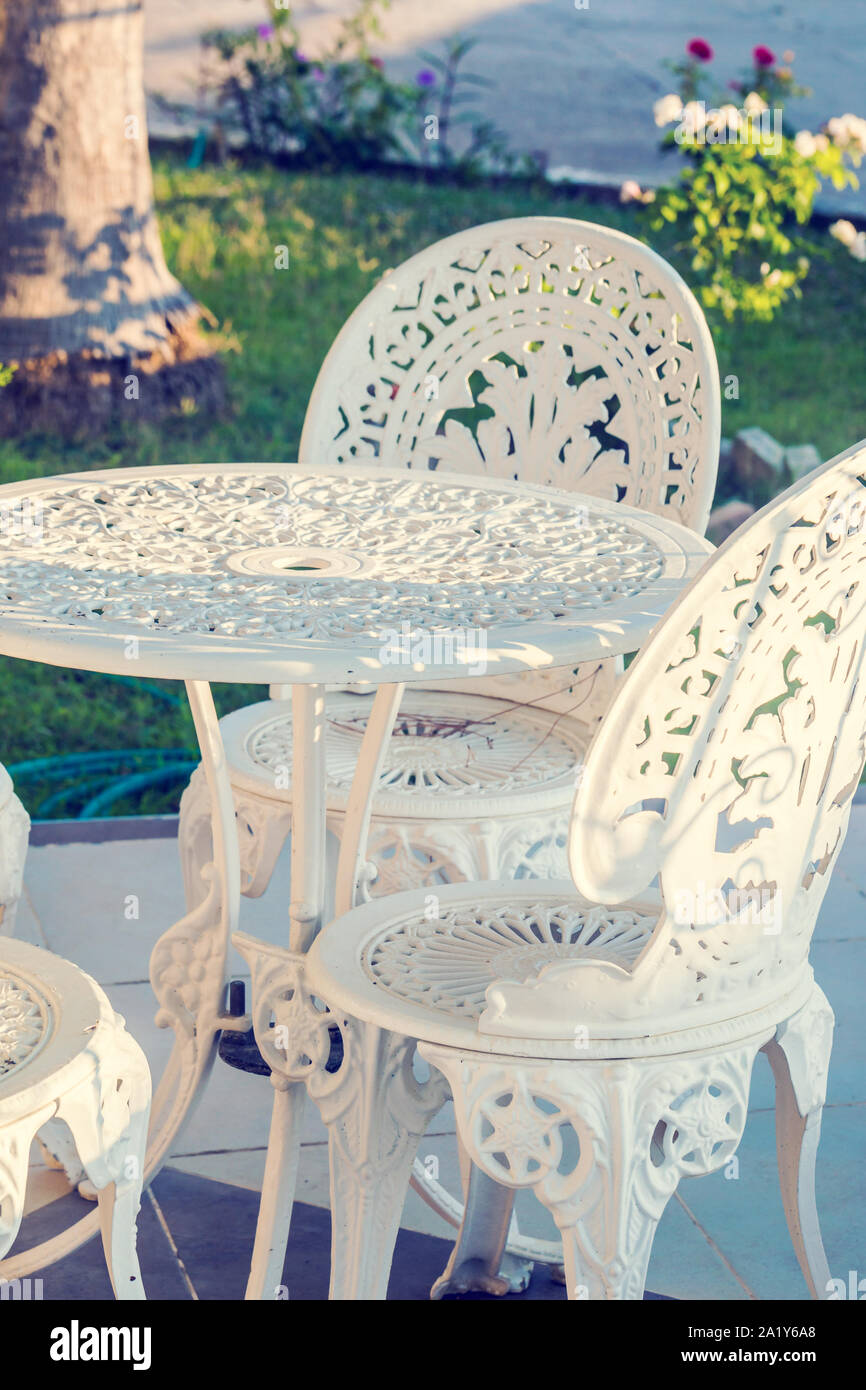 Vintage wrought iron garden table and chairs in a garden Stock