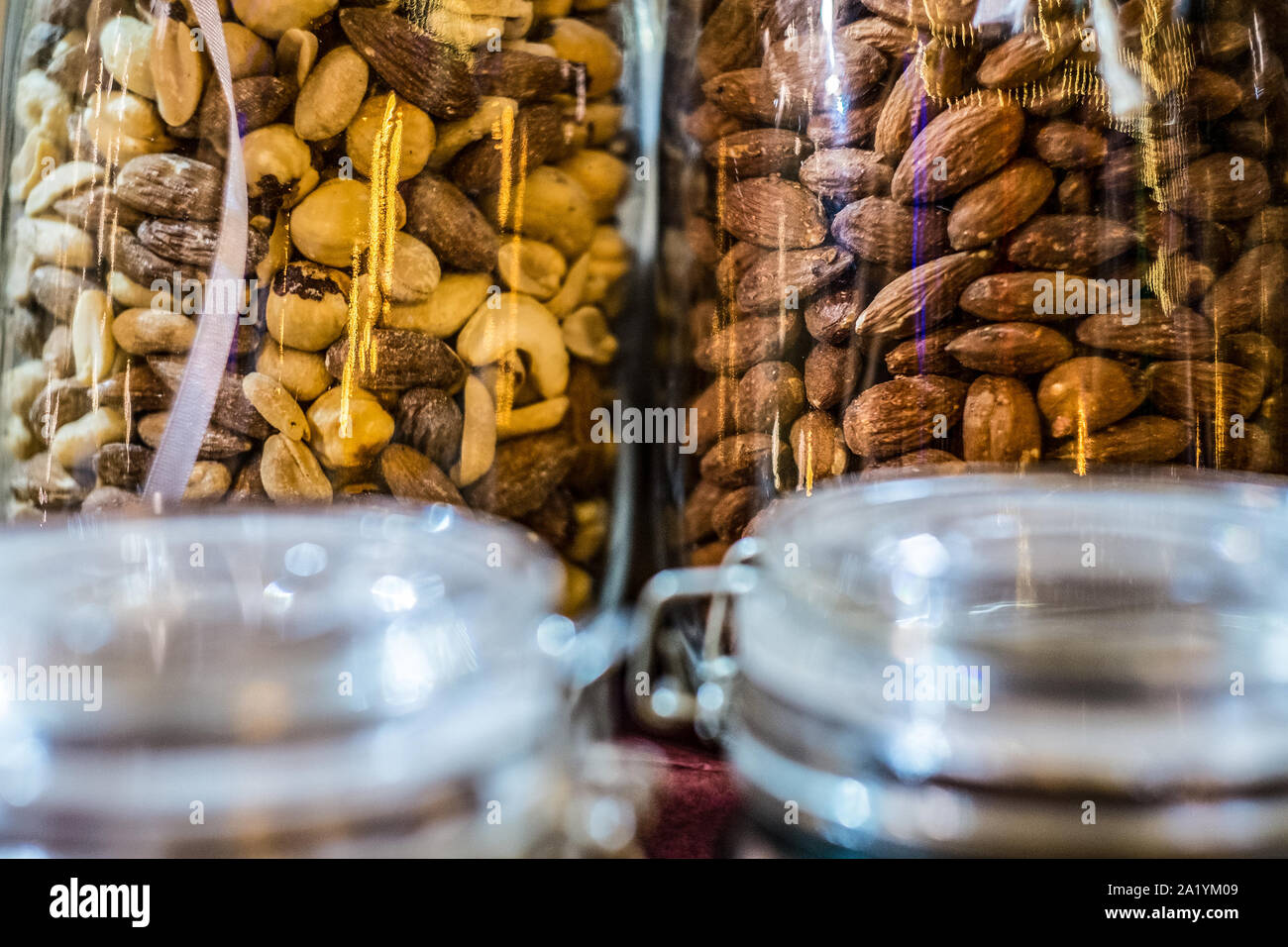 Different types of nuts and seeds in glass jar close up. A variety of nuts in glass jars. Stock Photo