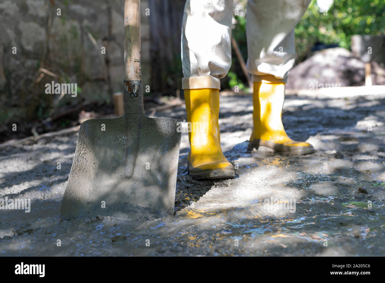 Construction worker in yellow rubber boots at the construction site, compacting the concrete Stock Photo