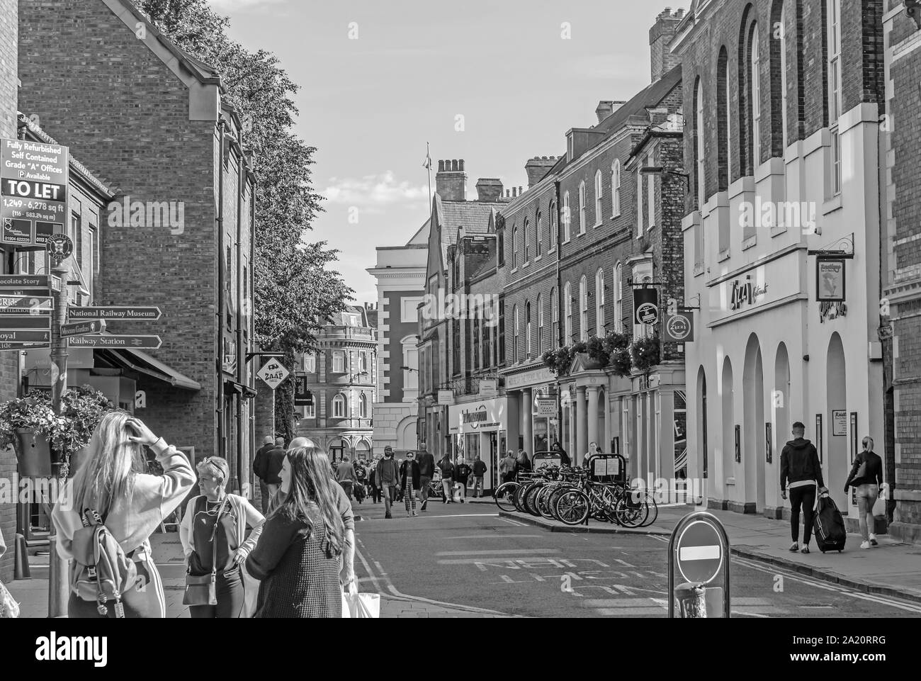 A street scene at the junction of Lendal and Museum Street in York. Shoppers mingle under a signpost and historic buildings line the street. Stock Photo