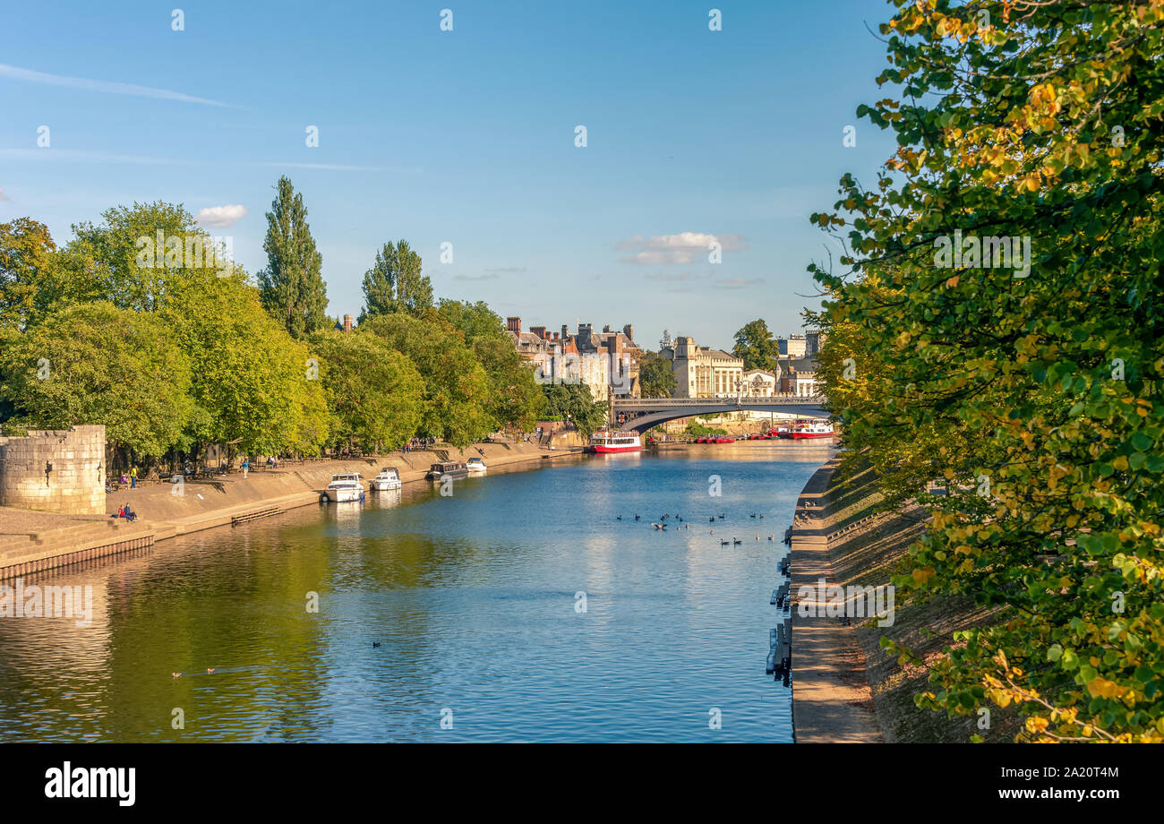 A view down the River Ouse in York to Lendal Bridge. An ancient defensive tower is in the foreground and ducks are on the water.  Boats are moored to Stock Photo
