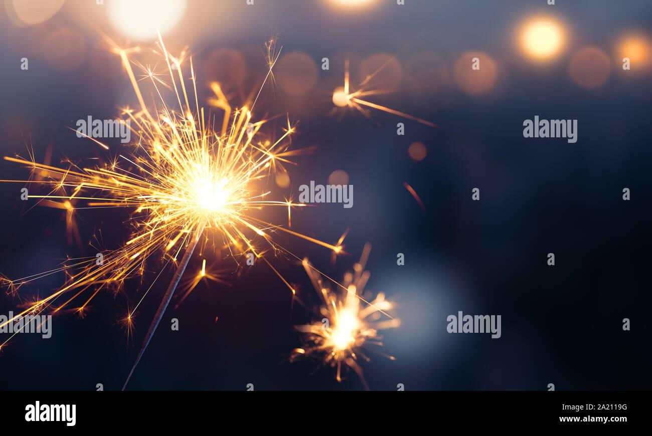 Glittering burning sparkler against blurred bokeh light background Stock Photo