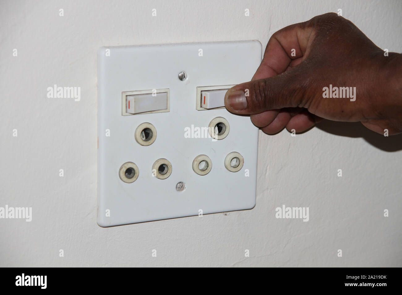 Close-up of hand pressing a white double power socket, South Africa. Stock Photo