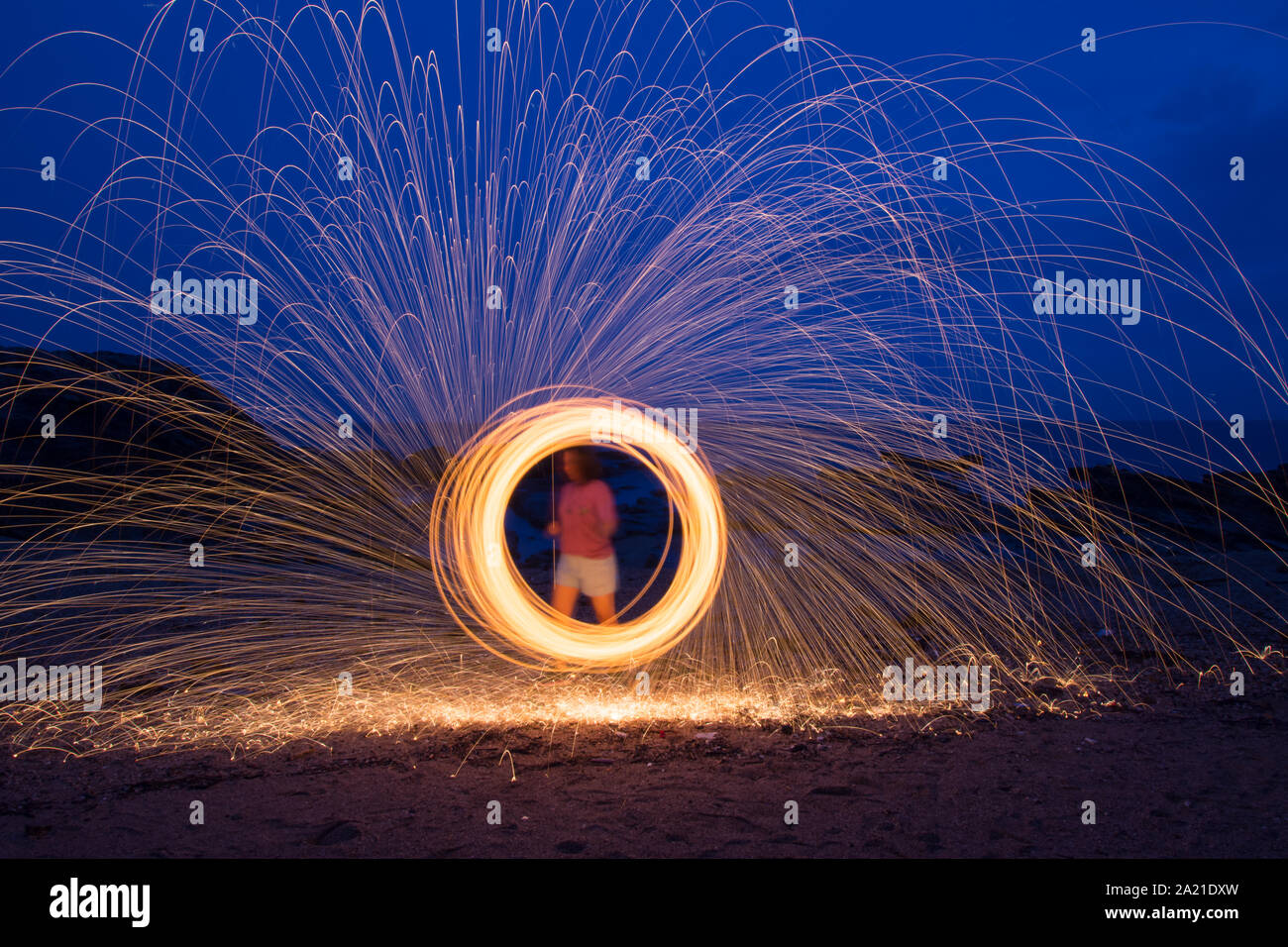 A woman doing circular spinning light painting using steel wool at night on the beach. Stock Photo