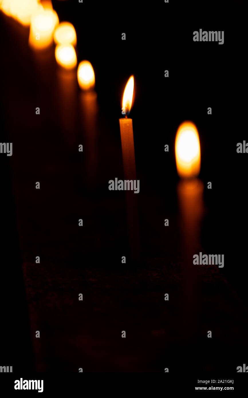Beautiful candles burning in a row or line pattern at a temple or church during Diwali celebration or ceremony at night. Background stock photo of fes Stock Photo