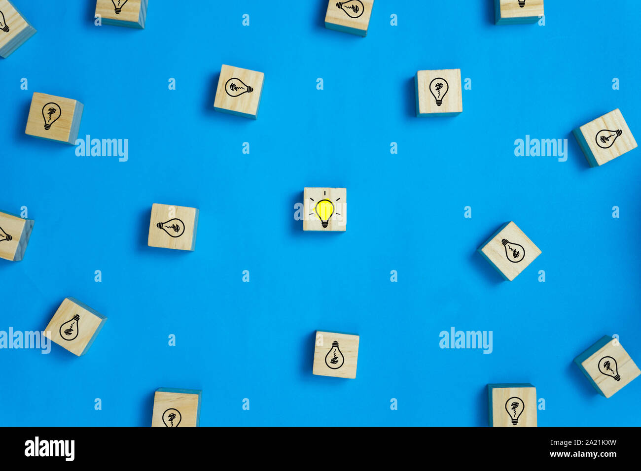 Creative ideas concept. Conceptual different thinking or leadership. One shining light bulb In the middle between many light bulb goes out on wooden b Stock Photo