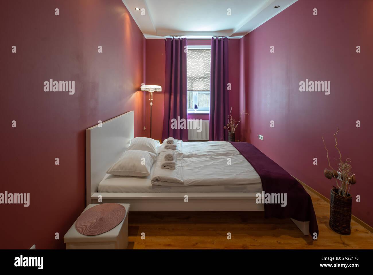 Modern bedroom in scarlet tones. Window with curtains. Floor lamp. Stock Photo