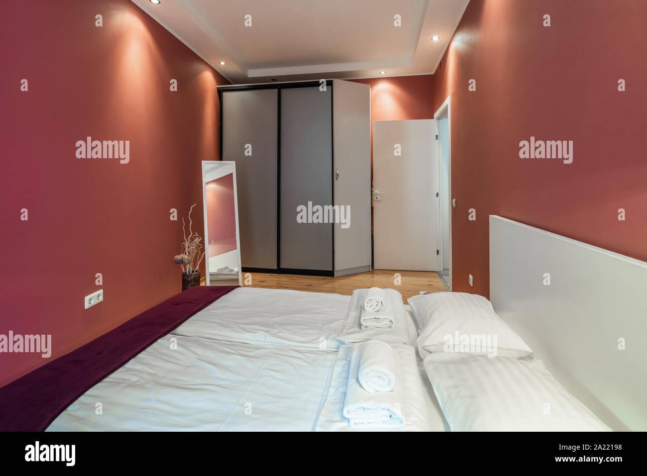 Modern bedroom in scarlet tones. Floor mirror. Stock Photo