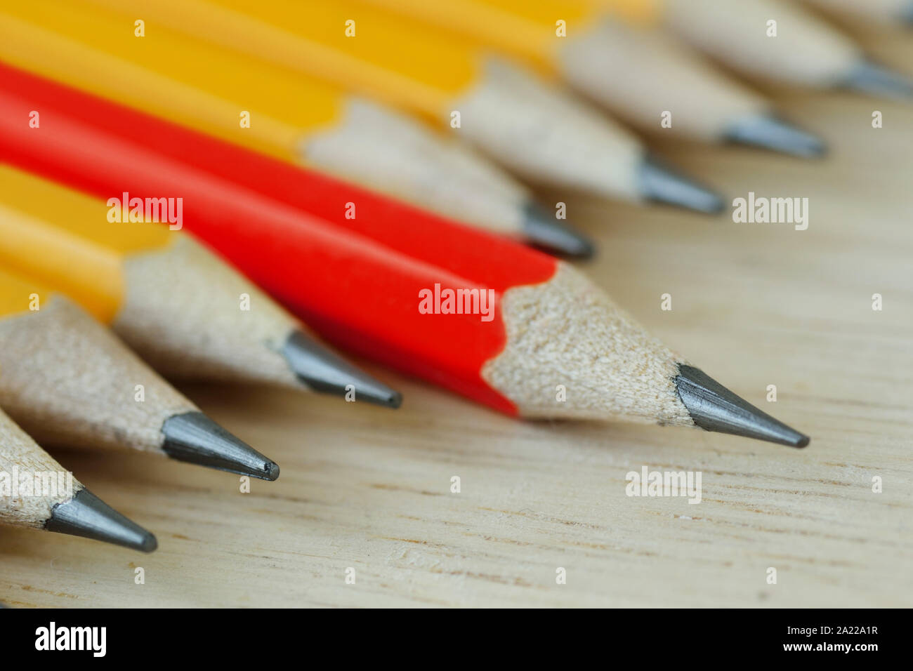 Red pencil standing out from croud of yellow pencils - Think different and leadership concept Stock Photo