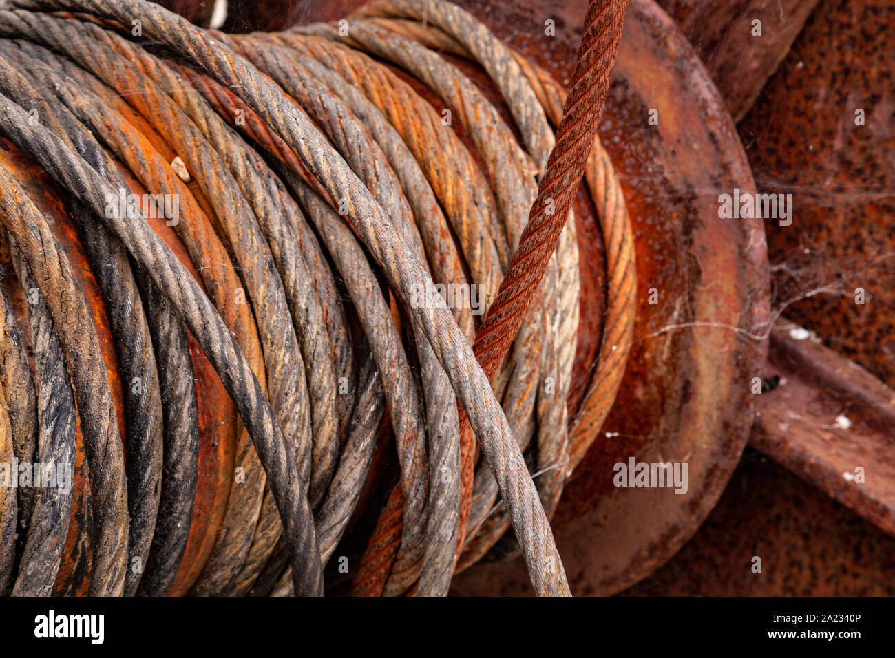 Old rusty cable drum and steel cable at Charlestown, Cornwall Stock Photo