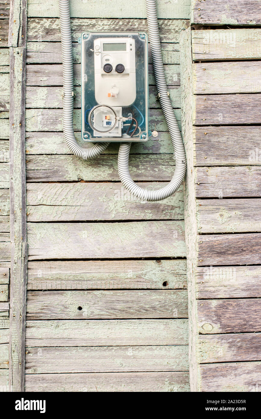 Modern electrical meter hanging on the old wooden house in the village outdoors Stock Photo