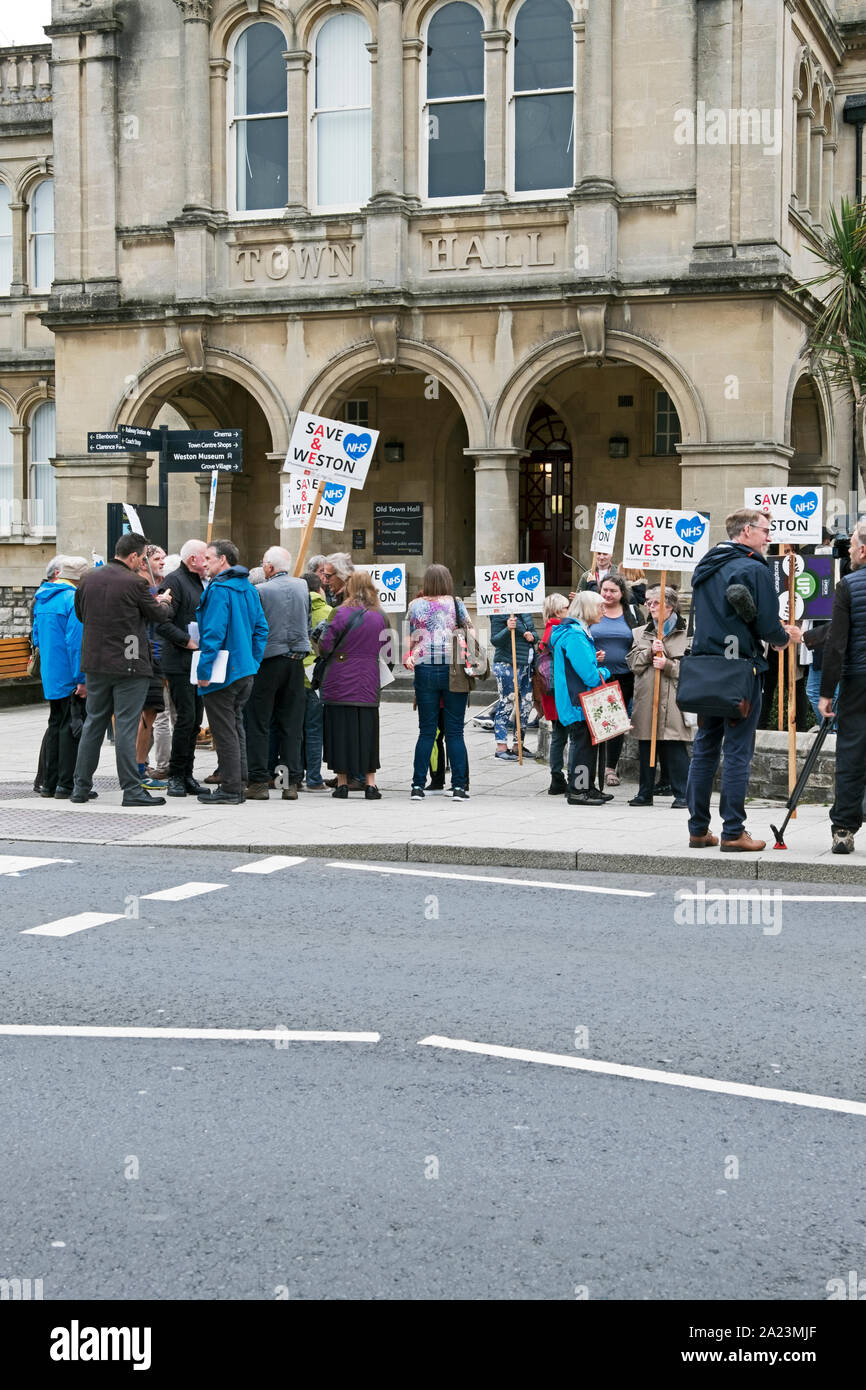 Weston-super-Mare, UK. 30 September 2019. Demonstrators protest against Bristol, North Somerset and South Gloucestershire Clinical Commissioning Group's plans for the future of Weston General Hospital outside the Town Hall where a meeting of North Somerset Council's Health Overview and Scrutiny Panel was taking place. The panel voted to recommend that the council refer the plans to the Secretary of State for review. Stock Photo