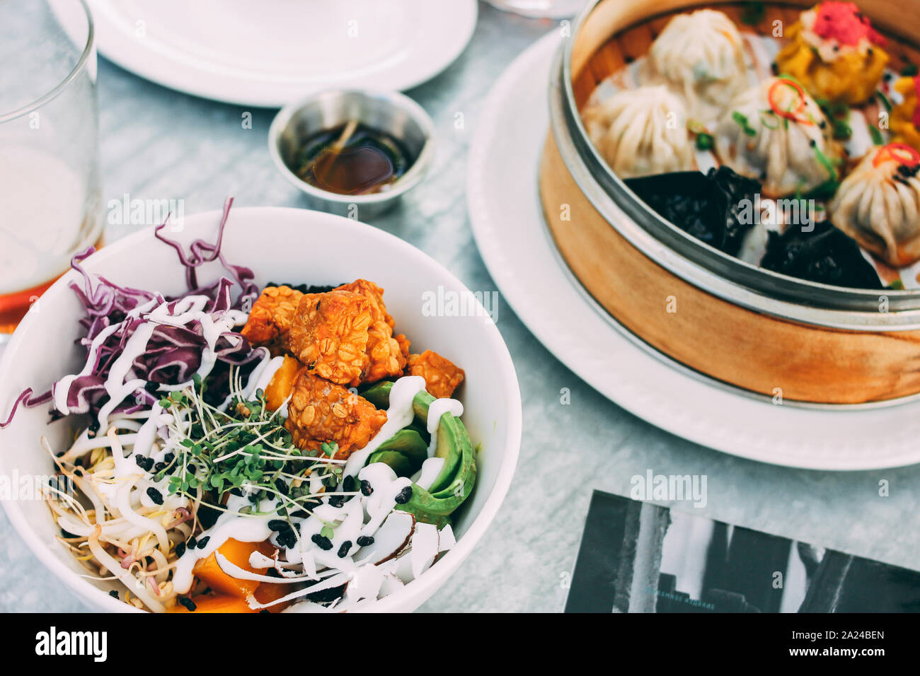 Pan-Asian food - vegetable salad bowl and different dim sums. Lunch for two with beer Stock Photo