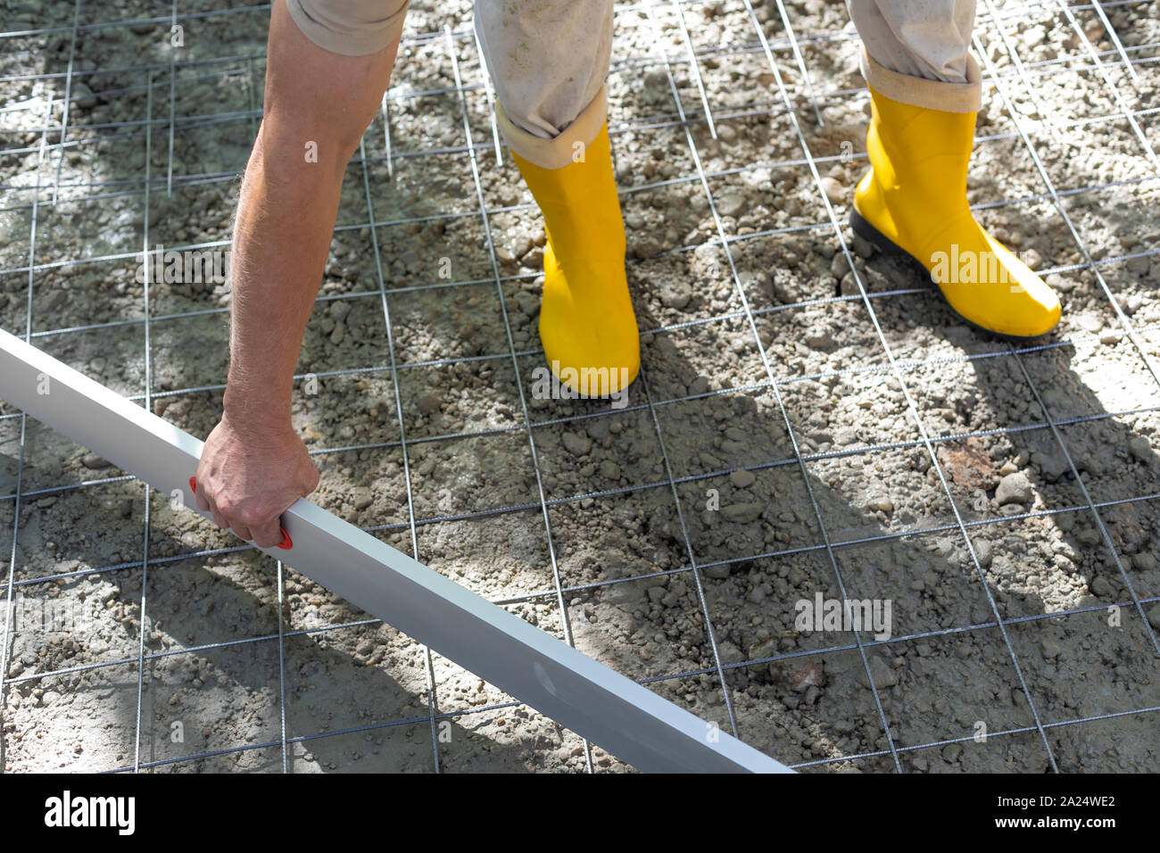 Construction worker in yellow rubber boots at the construction site, straighten and smoothing the concrete Stock Photo