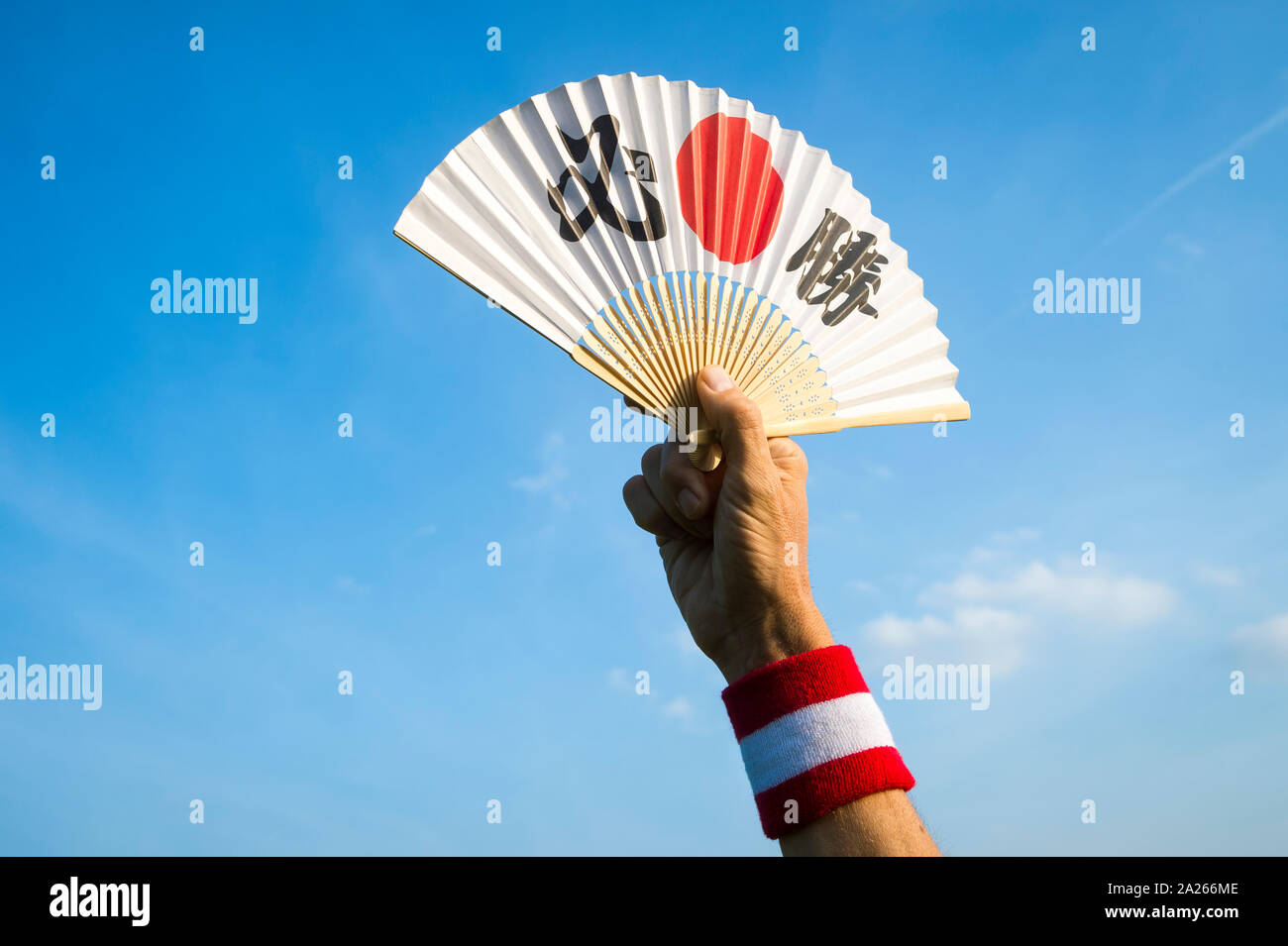 Hand of sports supporter with Japan flag colors wristband holding fan decorated with kanji characters spelling out hisshō, certain victory in English Stock Photo