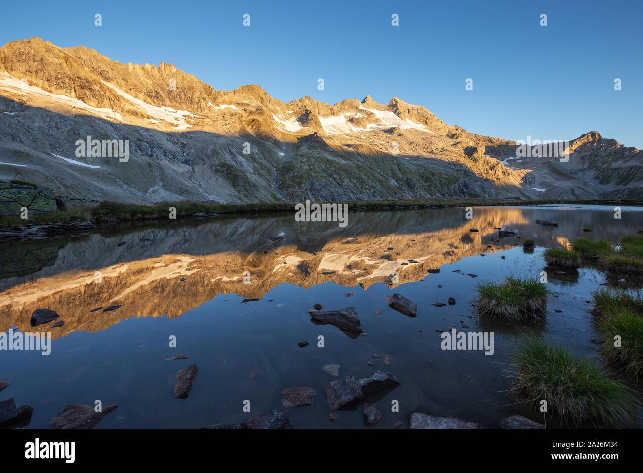 Peaks reflected on alpine lake. Reichenspitzgruppe. Reichenspitze peak. Sunrise sunlight on peaks and glaciers. Hohe Tauern Nationalpark. Stock Photo