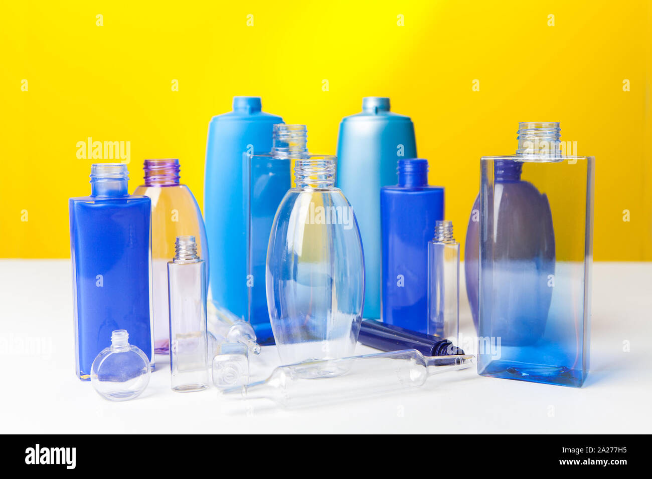 Group of empty plastic bottles, ampouls and vials,  of various sizes and colors. On yellow background Stock Photo