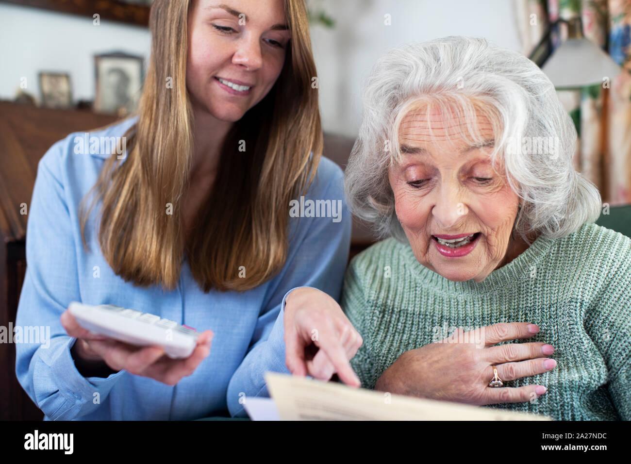 Woman Helping Senior Neighbor With Bills And Paperwork Stock Photo