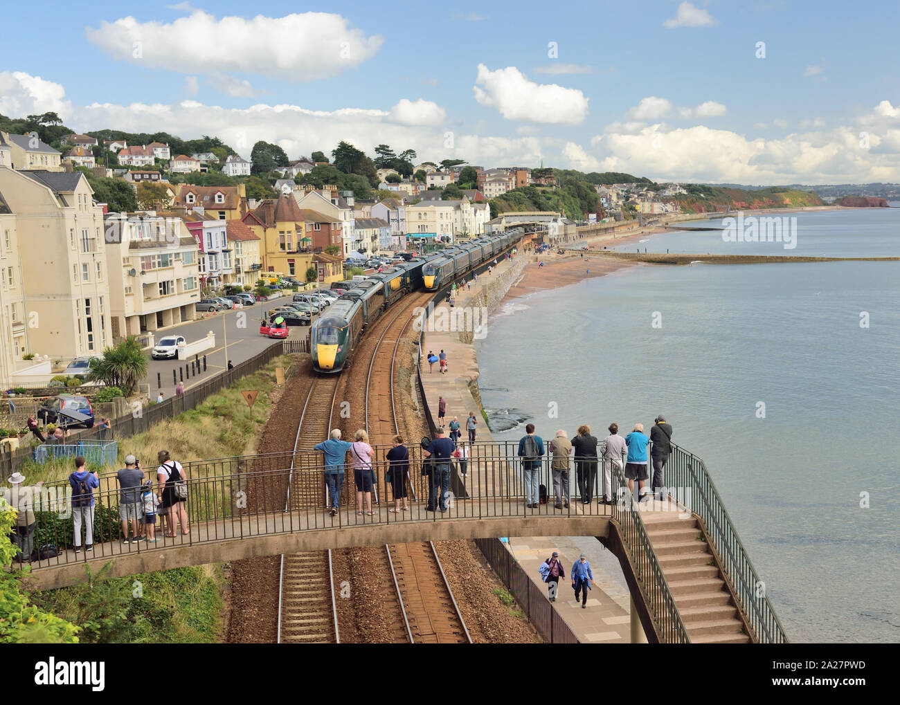 Great Western Intercity Express trains passing at Dawlish, watched by people on a footbridge. Stock Photo