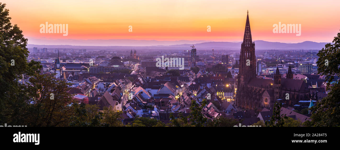 Germany, XXL panorama of skyline of freiburg im breisgau by night after sunset with red sky in magical twilight from above Stock Photo