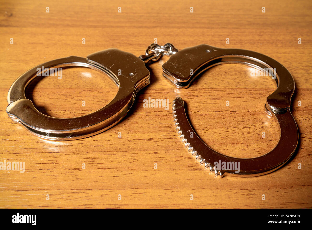Open handcuffs on a wooden table close-up Stock Photo