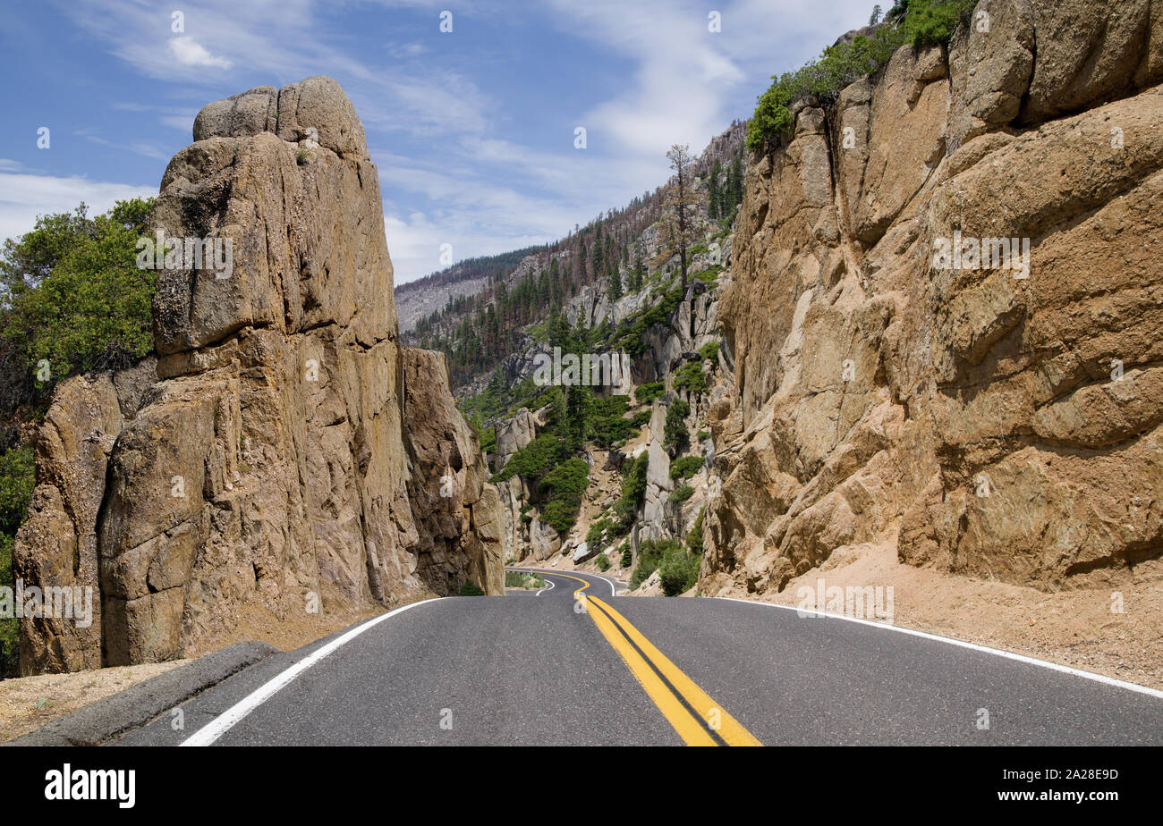 California Scenic Mountain Road:  A two lane highway passes through a cut between large rocks as it crosses the Sierra Nevada Mountains. Stock Photo