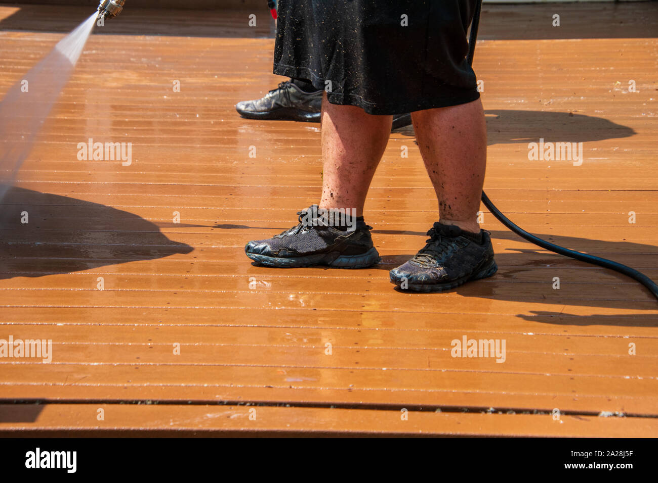 Legs of a man wearing black shorts washing the dirt off of a brown wooden deck with a wide spray of water from a metal nozzle. The man is wearing blac Stock Photo
