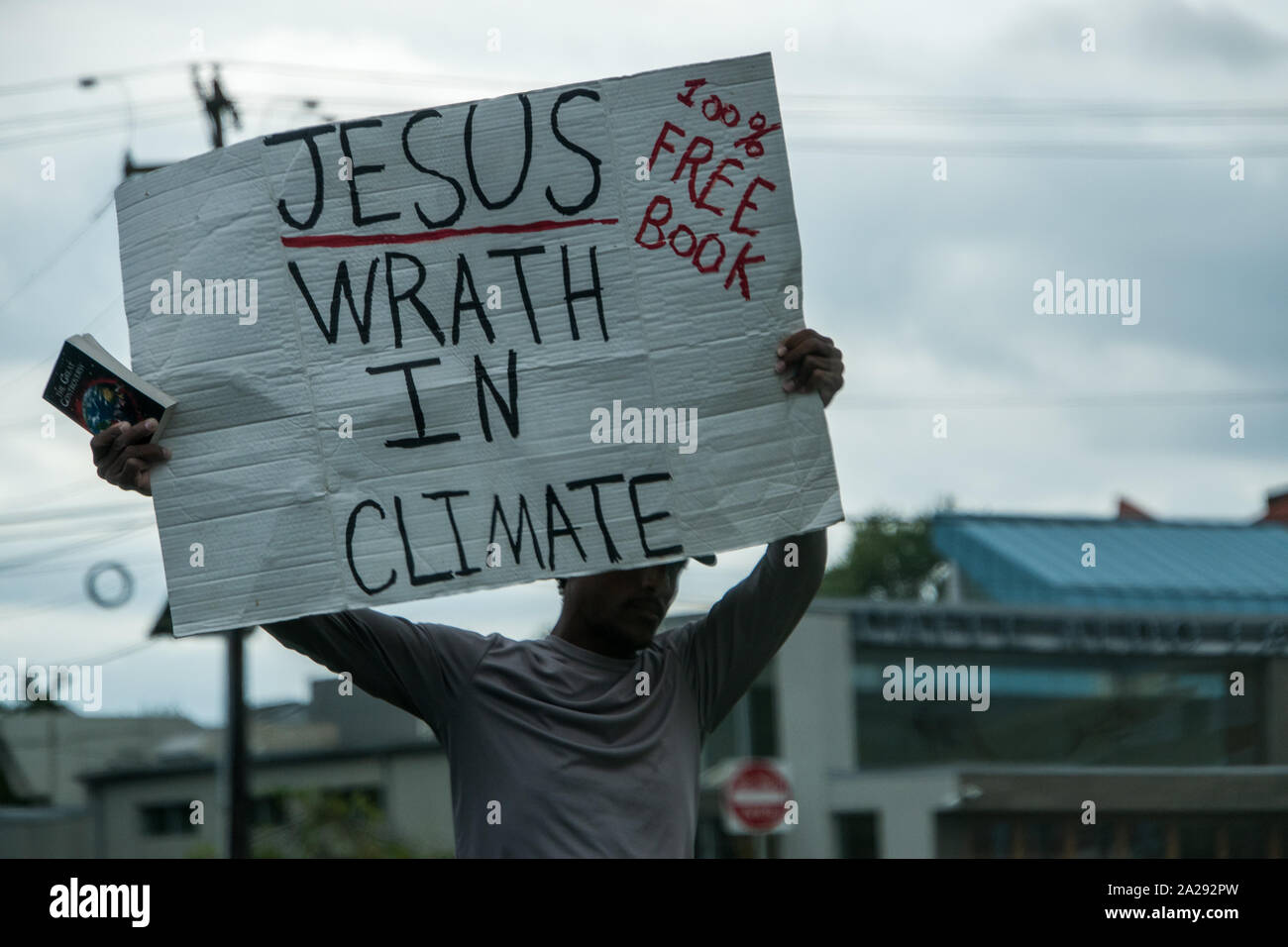 Cherry Hill, New Jersey - September 30, 2019: A black male was seen standing by the side of a busy road with a sign that says Jesus Wrath In Climate. Stock Photo