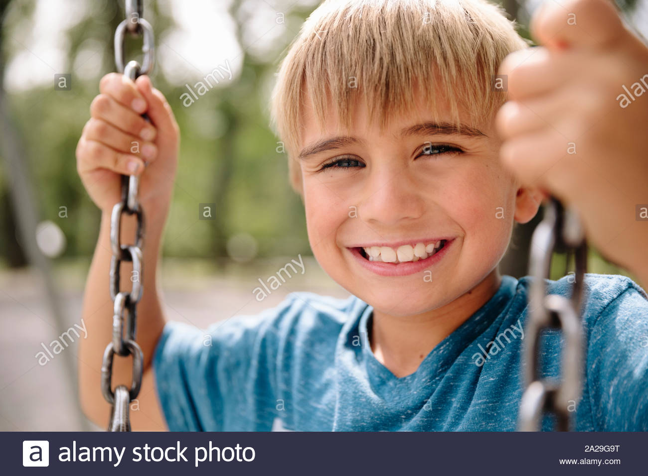 Portrait of young boy sitting on swing smiling towards camera Stock Photo