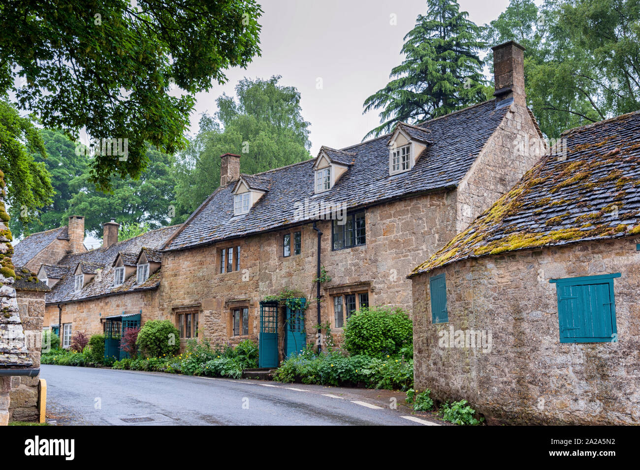 Typical pretty cottages with climbing plants with yellow Cotswold limestone walls and slate roof with garden of roses in Snowshill, Cotswolds England Stock Photo