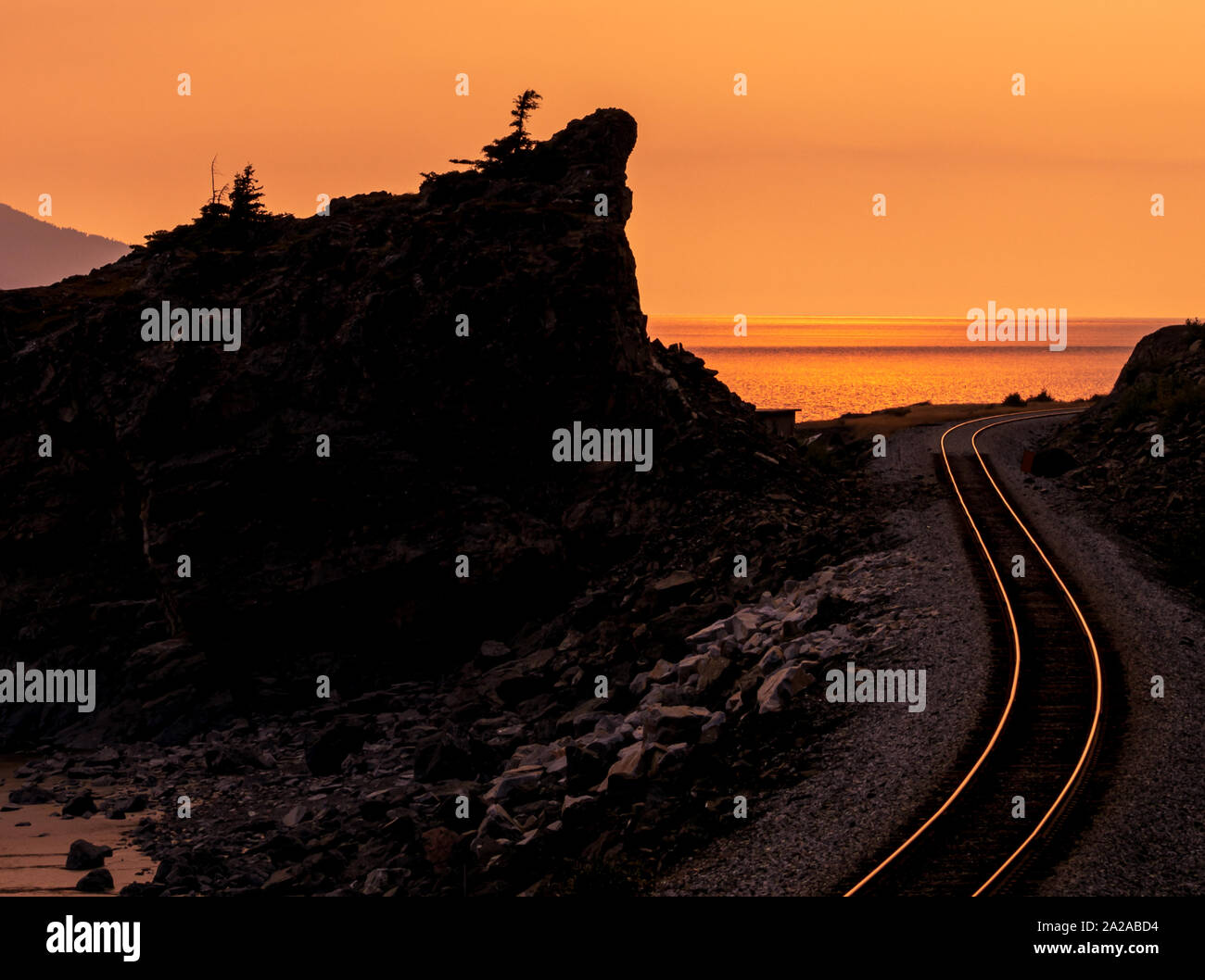 Railroad tracks on a beautiful rocky coastline with sunset and steel tracks glowing orange and yellow. Turnagin Arm, Seward Highway, Alaska. Stock Photo